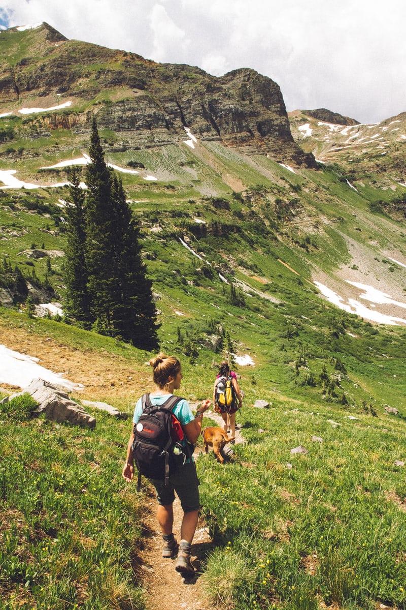 twee au pair meiden lopen door een bergdal van gras
