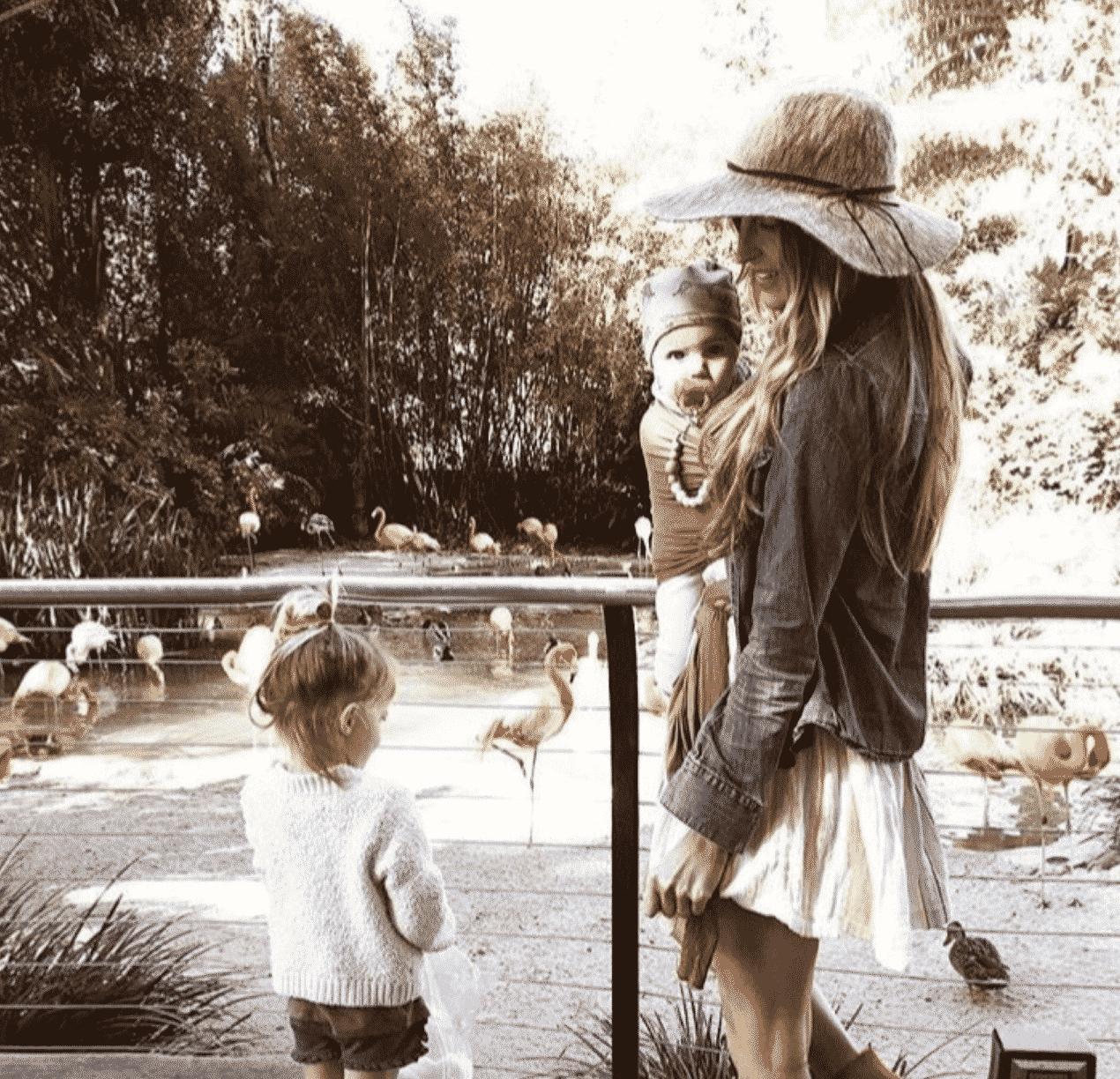 au pair staat bij de dierentuin met flamingo's en een baby op haar buik. De au pair heeft op haarhoofd een zomerse zomerhoed.