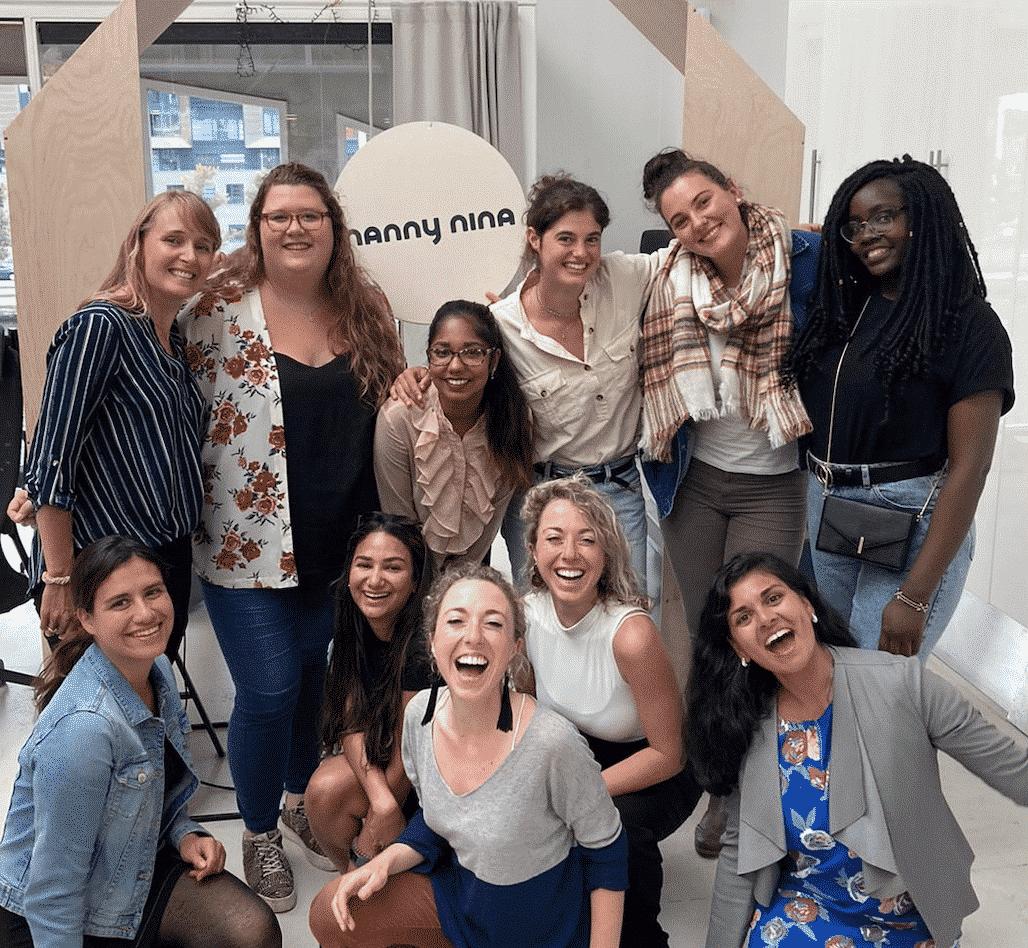 Groepje van 10 Au pairs van over heel de wereldstaan in een groepje op het nanny nina kantoor voor het logo van nanny nina au pair bureau en lachen in de camera