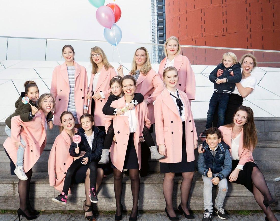 Feestelijke groepsfoto van vrouwen in roze jassen die kinderen dragen