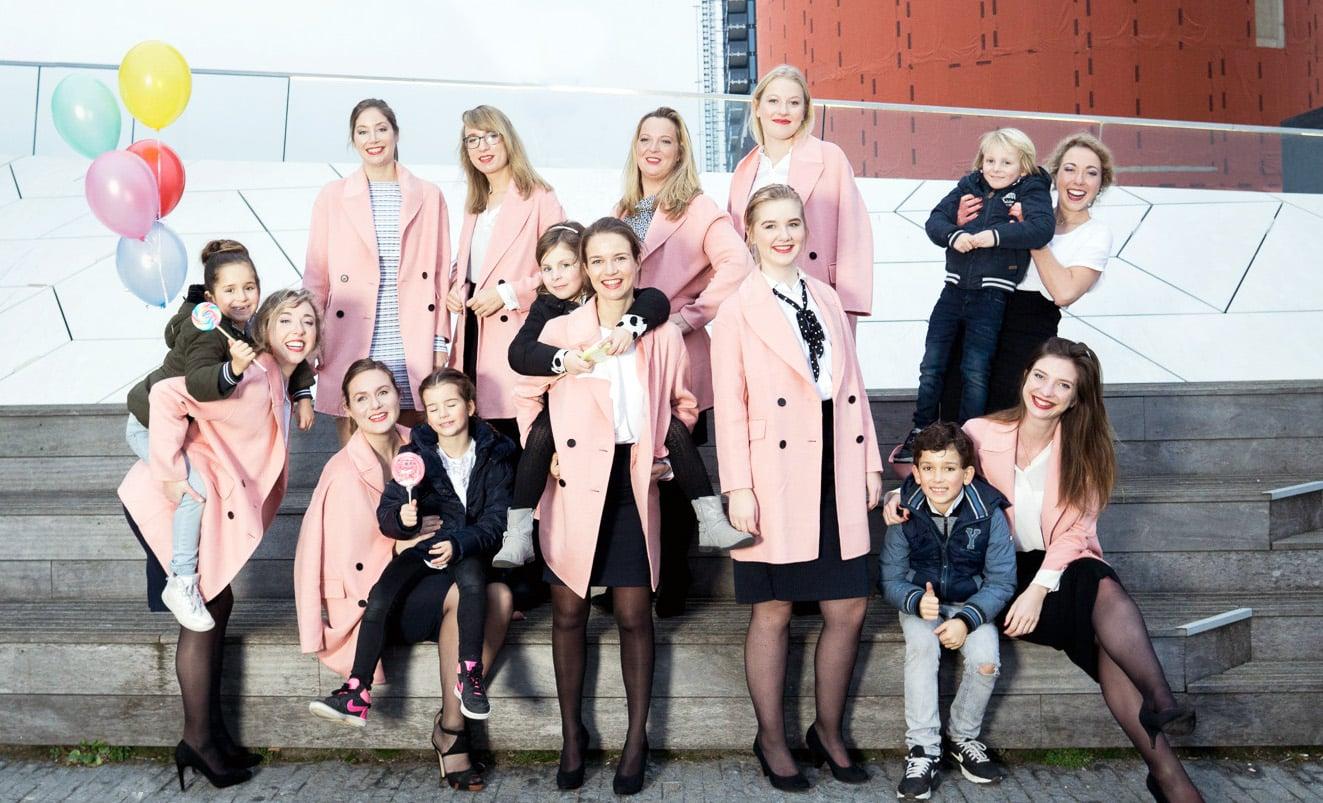 Groep dames met roze regenjassen en ballonnen