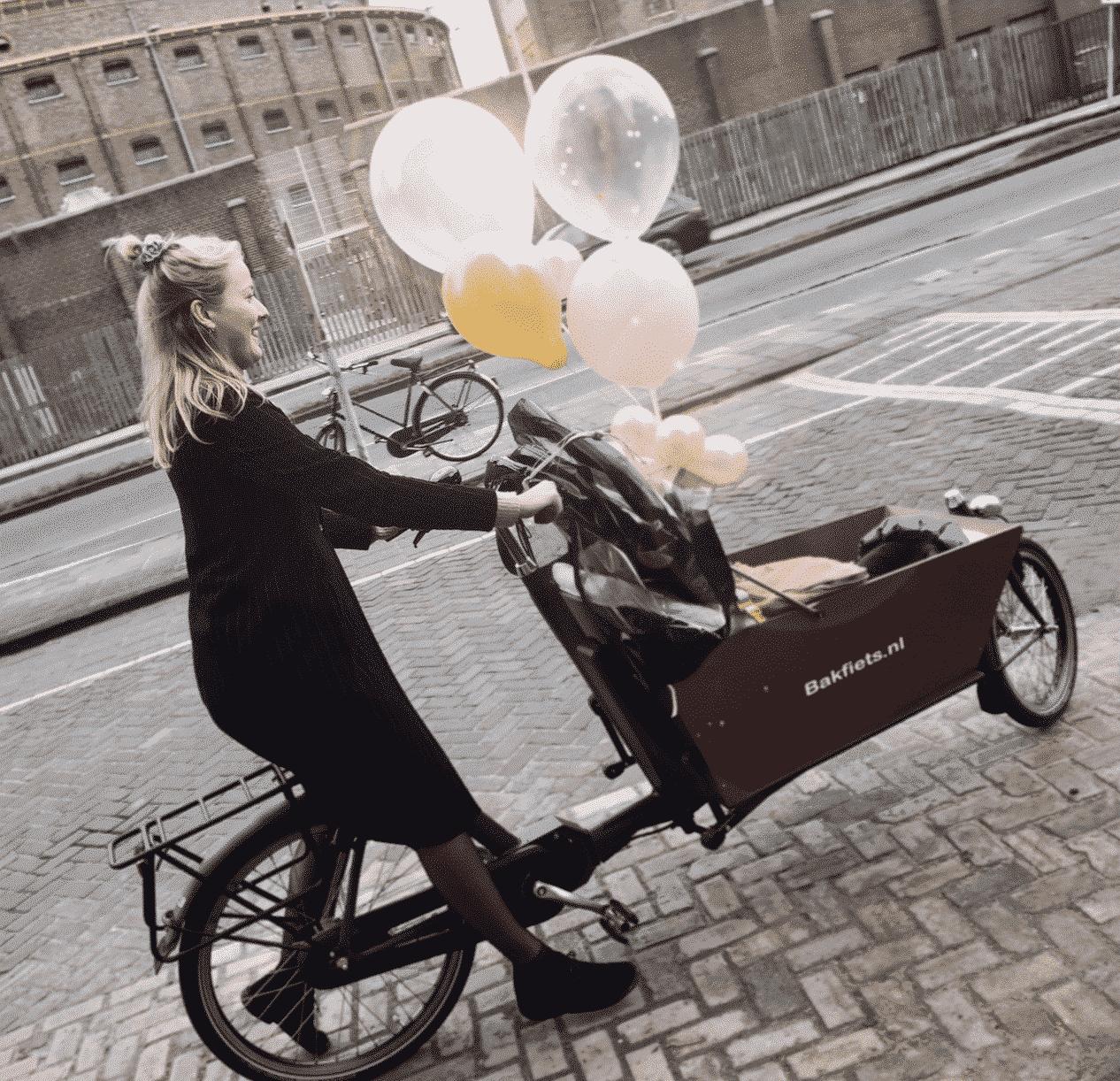 gastouder van Nanny Nina rijdt met de kinderen in een bakfiets naar de speelafspraak. De gastouder heeft blond haar en balonnen aan de bakfiets.