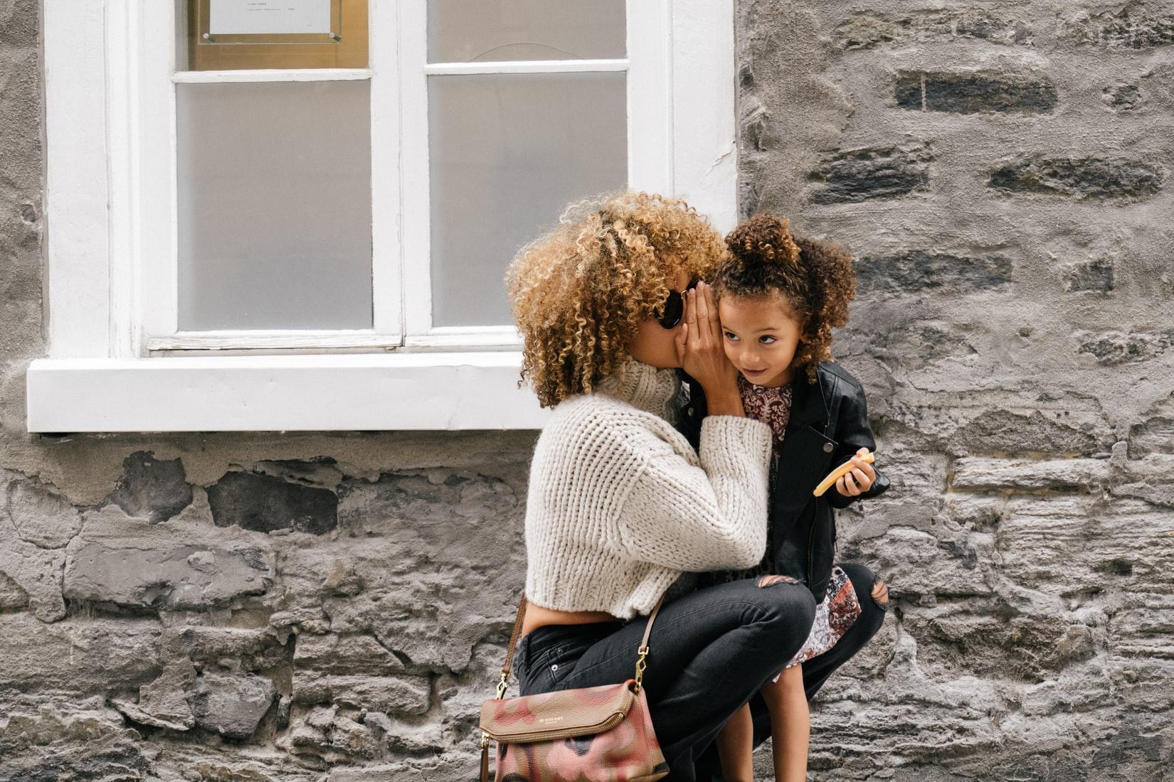 gastouder met donkere krullen knuffels oppaskindje buiten in de zon knuffelt kindje en de gastouder fluistert een geheimpje in het oor van het meisje van 6 jaar oud. De gastouder staat voor het kantoor van Nanny Nina