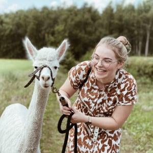 Oppas Nanny Nina met lama aan tuigje lachend