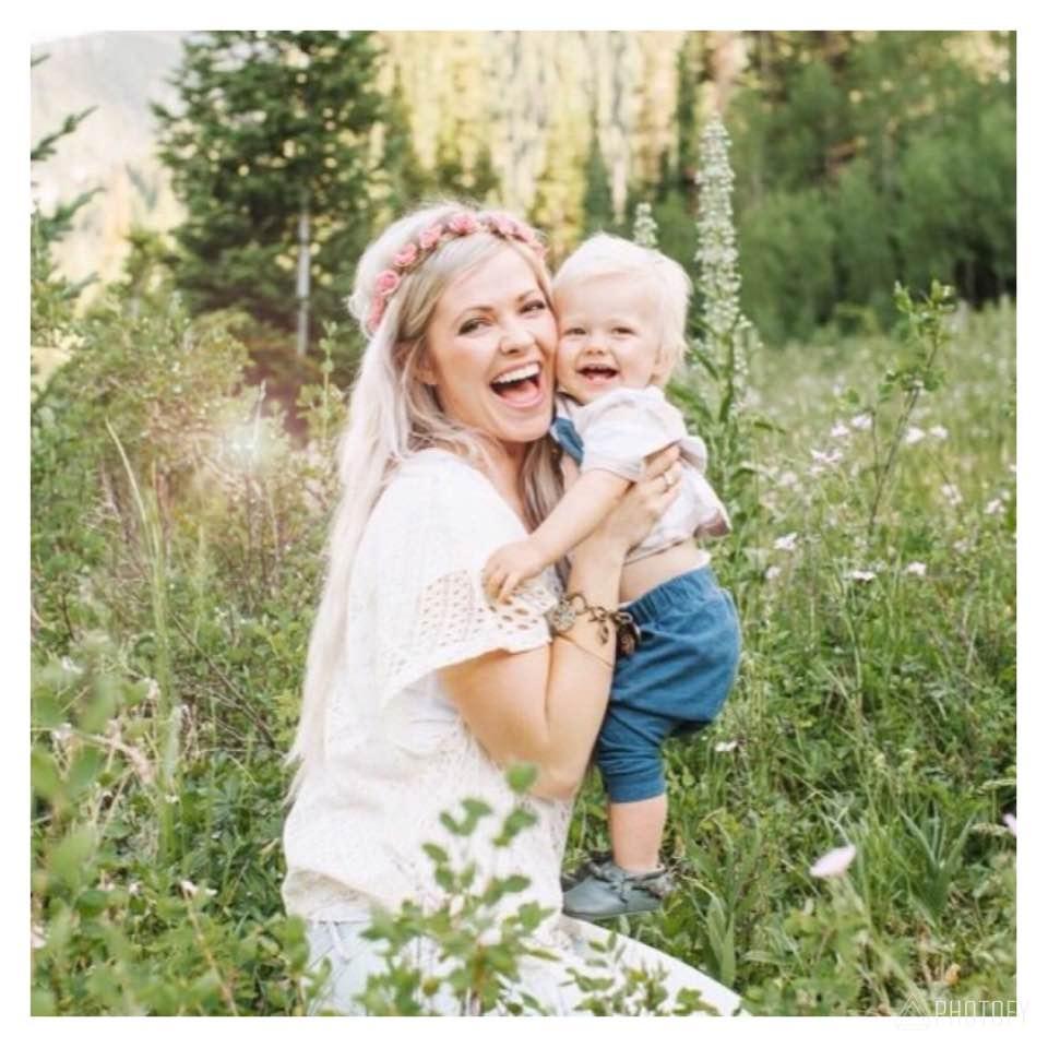 oppas houdt kindje vast terwijl ze in gras zit met bloemen in haar haar