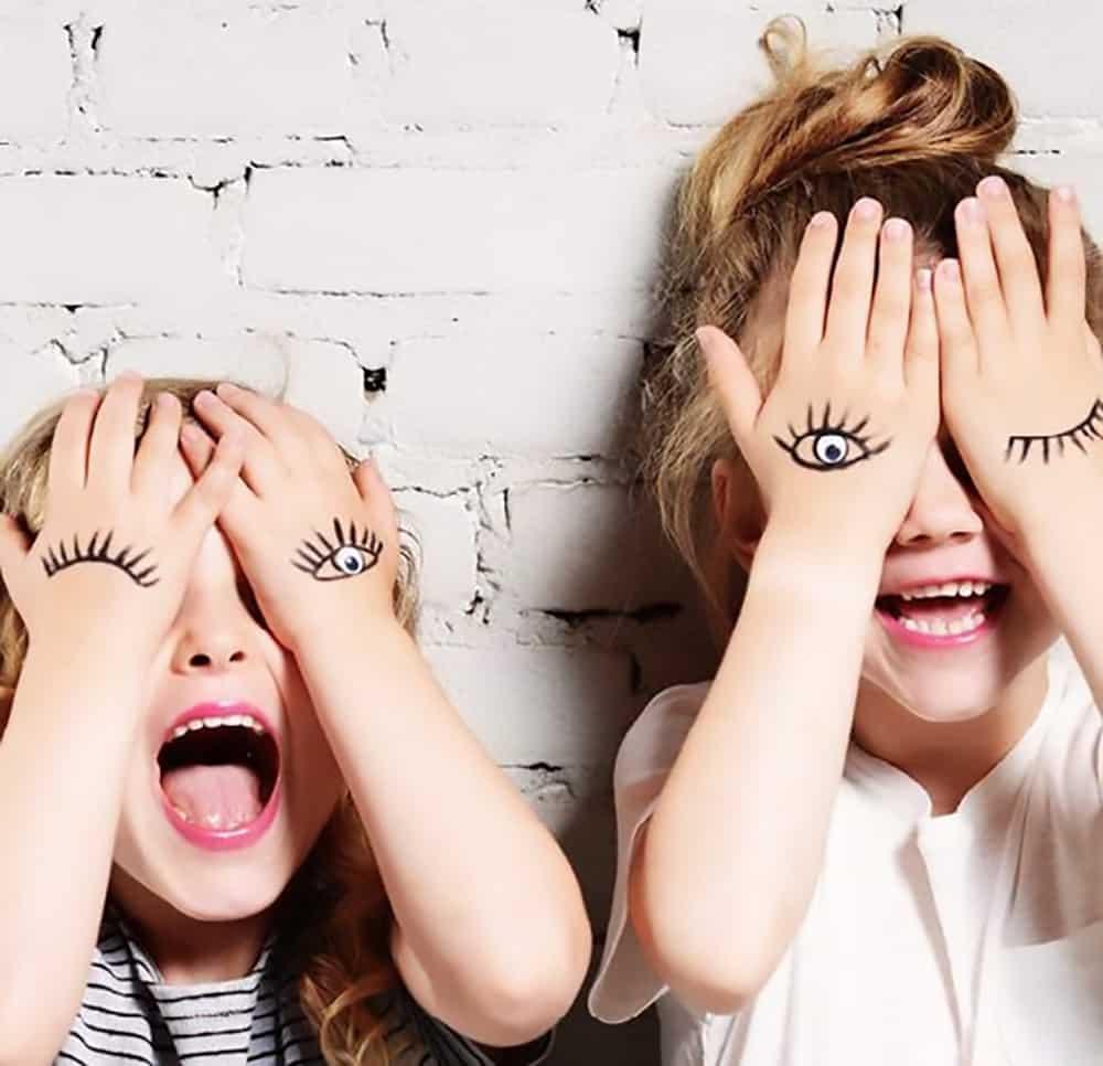 Kindjes lachen en knipogen met getekende figuurtjes op hun handjes