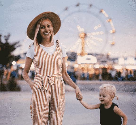 vaste oppas van nanny nina haalt kindje op bij de kermis ze draagt een witte orange broek staat op de kermis en hodut handje vast van een kindje waar ze wekelijks op past.