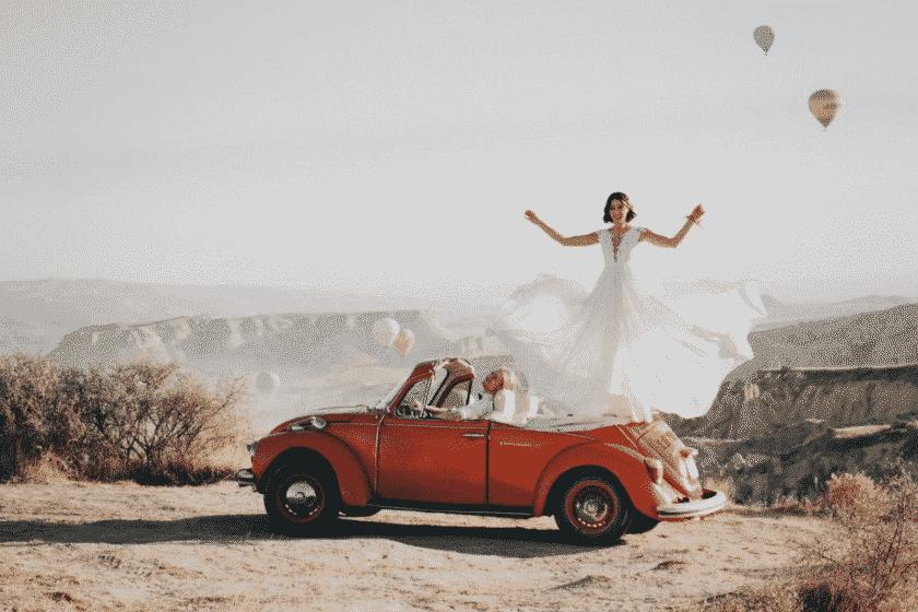 bruid staat op rode auto met luchtbalonnen op de achtergrond en lacht naar de oppas die de foto neemt
