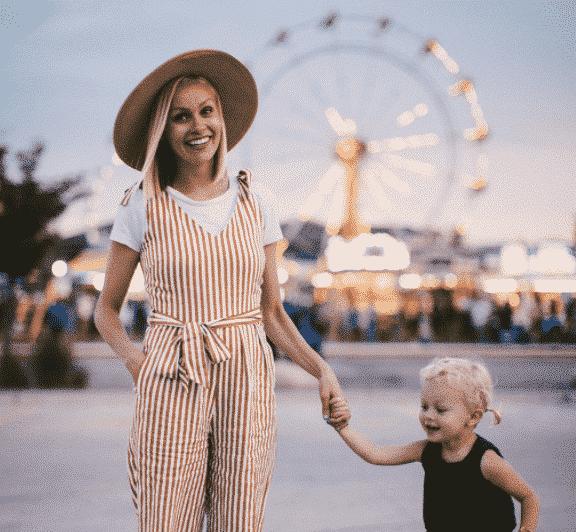 Au pair samen met haar host kid op de kermis of oppaswerk gezocht met kindje aan haar arm